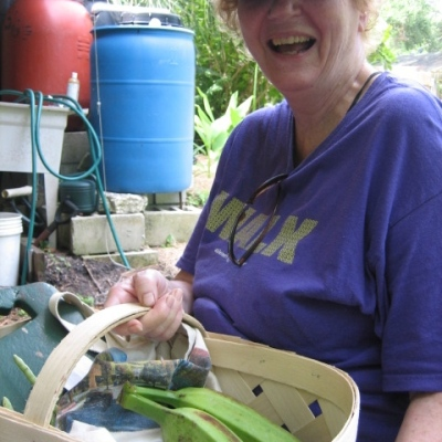 Diane, happy after a lovely morning learning worm maintenance, harvesting, chatting, and going home with a basket of produce - today's special - Florida bananas. cross between a plantain and a banana.